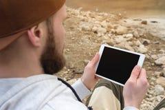 群众的特写镜头在一个棕色盖帽的在他的手上露天拿着一台白色片剂个人计算机 一个有胡子的人看 免版税库存图片