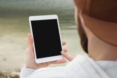 群众的特写镜头在一个棕色盖帽的在他的手上露天拿着一台白色片剂个人计算机 一个有胡子的人看 免版税图库摄影