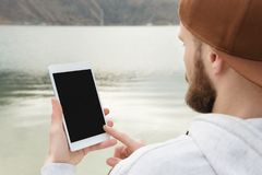 群众的特写镜头在一个棕色盖帽的在他的手上露天拿着一台白色片剂个人计算机 一个有胡子的人看 免版税库存照片