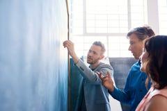 群策群力在一个黑板的三个同事在办公室 免版税库存照片