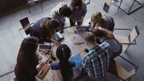 群策群力,如果创造性的混合的族种人在现代办公室 人顶视图站立近的桌的