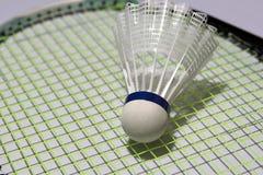 羽毛球塑料shuttlecock投入了羽毛球拍绿色网  图库摄影