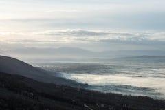 翁布里亚谷美丽的景色在一个冬天早晨,与雾覆盖物树和房子 库存图片