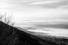 翁布里亚谷美丽的景色在一个冬天早晨,与雾覆盖物树和房子 免版税图库摄影