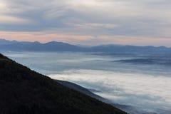 翁布里亚谷美好的鸟瞰图在一个冬天早晨,与雾覆盖物树和房子和温暖的颜色在天空 库存照片