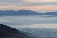 翁布里亚谷美好的鸟瞰图在一个冬天早晨,与雾覆盖物树和房子和温暖的颜色在天空 免版税库存图片