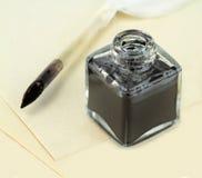 翎毛钢笔和玻璃墨水壶有纸的 免版税库存照片
