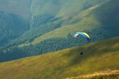 滑翔伞一前一后飞行在一个山谷在一个晴朗的夏日 滑翔伞在喀尔巴汗在夏天 免版税库存图片