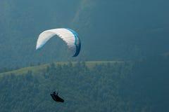 滑翔伞飞行在一个山谷在一个晴朗的夏日 库存照片