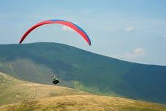 滑翔伞飞行在一个山谷在一个晴朗的夏日 图库摄影