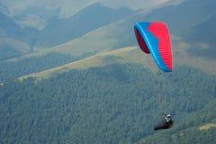 滑翔伞飞行在一个山谷在一个晴朗的夏日 免版税图库摄影