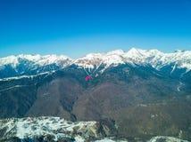 滑翔伞飞行在滑雪胜地的山 免版税库存照片
