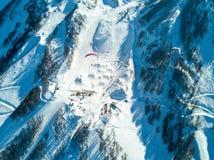 滑翔伞飞行在滑雪胜地的山 图库摄影