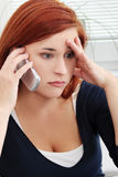 翻倒和担心的少妇联系由电话 库存图片