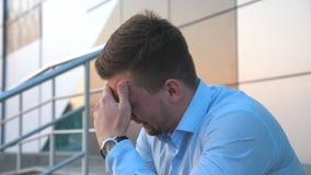 翻倒哀伤的商人侧视图坐台阶临近办公楼和哭泣 绝望年轻人得到了一非常坏