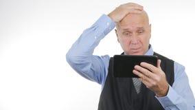 翻倒商人在片剂读了坏消息并且做紧张的手势 图库摄影