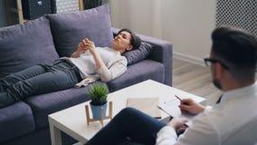 翻倒女孩谈论情感与说谎在长沙发的心理学家在办公室 股票视频