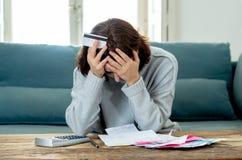翻倒年轻女人强调说关于信用卡债务和付款不愉快的认为的财务 库存图片