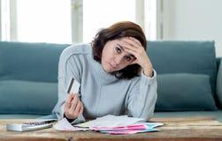 翻倒年轻女人强调说关于信用卡债务和付款不愉快的认为的财务 免版税库存照片