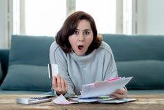 翻倒年轻女人强调说关于信用卡债务和付款不愉快的认为的财务 免版税库存图片