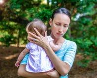翻倒母亲保护她的女儿 库存图片
