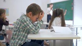 翻倒男小学生坐在一张书桌在教室在同学和女老师背景靠近黑板 影视素材