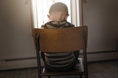 翻倒问题孩子坐胁迫的,消沉重音椅子概念 库存照片