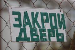 翻译:紧密门 板材由手做了在与在篱芭垂悬在村庄的题字的门 库存照片