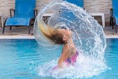 翻转在水池的女孩头发在阳光下 免版税库存照片