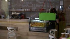 翻转在绿色在门的屏幕开放标志在早晨问候客户和接受命令的小咖啡店所有者- 股票录像