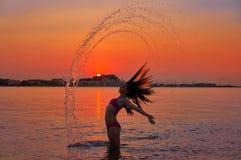 翻转头发轻碰的女孩在日落海滩 免版税库存图片