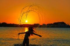 翻转头发轻碰的女孩在日落海滩 免版税库存照片
