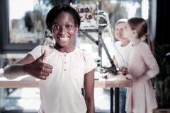 翻阅在审查的满意的女小学生机器人以后 免版税库存照片