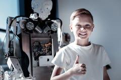 翻阅满意的孩子站立在机器人旁边和  图库摄影