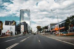 翼果,俄罗斯- 2016年8月07日:其中一大街在有现代房子的翼果城市和购物中心和购物中心 免版税库存照片