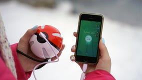 翼果,俄罗斯- 2016年12月15日:演奏pokemon的妇女在他的iphone去 pokemon是与元素的多功能单放机的比赛  库存照片