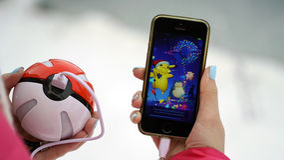 翼果,俄罗斯- 2016年12月15日:演奏pokemon的妇女在他的iphone去 pokemon是与元素的多功能单放机的比赛  免版税图库摄影