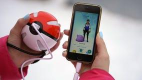 翼果,俄罗斯- 2016年12月15日:演奏pokemon的妇女在他的iphone去 pokemon是与元素的多功能单放机的比赛  库存图片