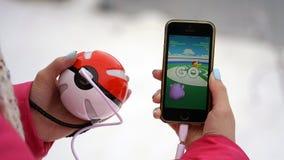 翼果,俄罗斯- 2016年12月15日:演奏pokemon的妇女在他的iphone去 pokemon是与元素的多功能单放机的比赛  免版税库存照片