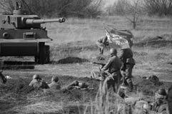 2018-04-30翼果,俄罗斯 苏联军队的战士攻势与一面旗子的在德国军队的位置 reco 免版税库存照片