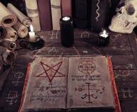 老不可思议的书和黑蜡烛在巫婆桌上 免版税库存照片