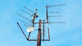 老与指向另外在蓝色sk的方向捉住的电视信号波浪的许多天线的葡萄酒生锈的电视帆柱 免版税库存图片