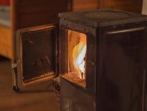 老与灼烧的火焰木头的金属开放火炉门 免版税库存图片