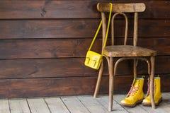 老与黄色老鞋子的葡萄酒维也纳棕色椅子和黄色小袋子在棕色老顶楼 免版税库存照片