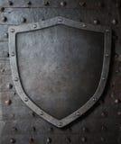 老中世纪徽章在金属门背景的盾 免版税库存照片