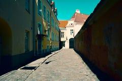 老中世纪狭窄的街道在有破旧的墙壁的塔林,爱沙尼亚 库存图片