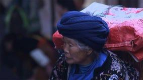 老中国女人运载的袋子乡下画象  云南 中国 免版税库存图片