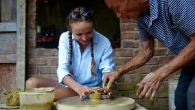 老主人引导做泥罐的女孩手指在轮子 股票视频