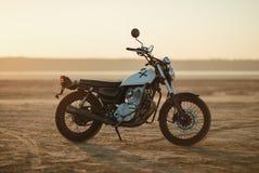 老习惯美丽的咖啡馆竟赛者摩托车在日落或日出的沙漠 免版税库存图片