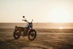 老习惯美丽的咖啡馆竟赛者摩托车在日落或日出的沙漠 免版税库存照片